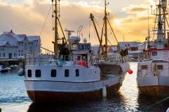 Fischerboot bei Schneefall und Sonnenuntergang